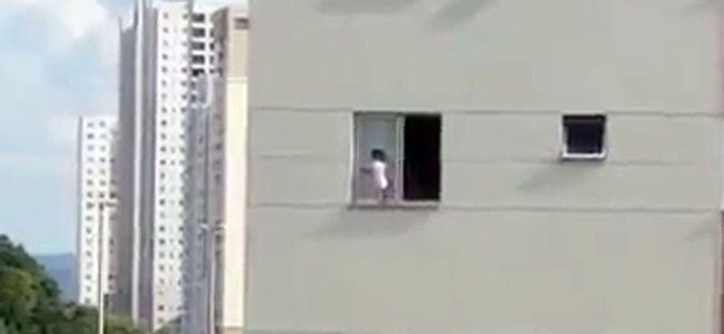 Imaginile coplesitoare cu un bebelus care se joaca pe pervazul din exteriorul ferestrei, la etajul trei