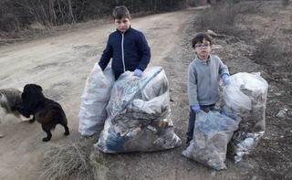 Doi copii au adunat toate gunoaiele de pe marginea drumului pe care merg spre scoala